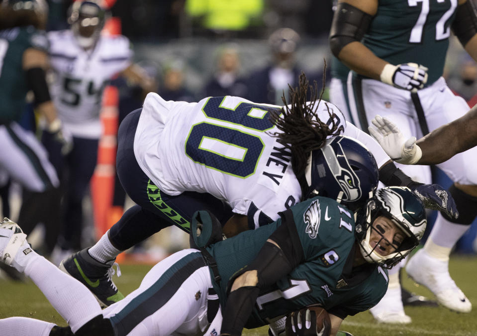 Jan 5, 2020; Philadelphia, Pennsylvania, USA; Philadelphia Eagles quarterback Carson Wentz (11) is hit by Seattle Seahawks defensive end Jadeveon Clowney (90) during the first quarter in a NFC Wild Card playoff football game. Mandatory Credit: Bill Streicher-USA TODAY Sports