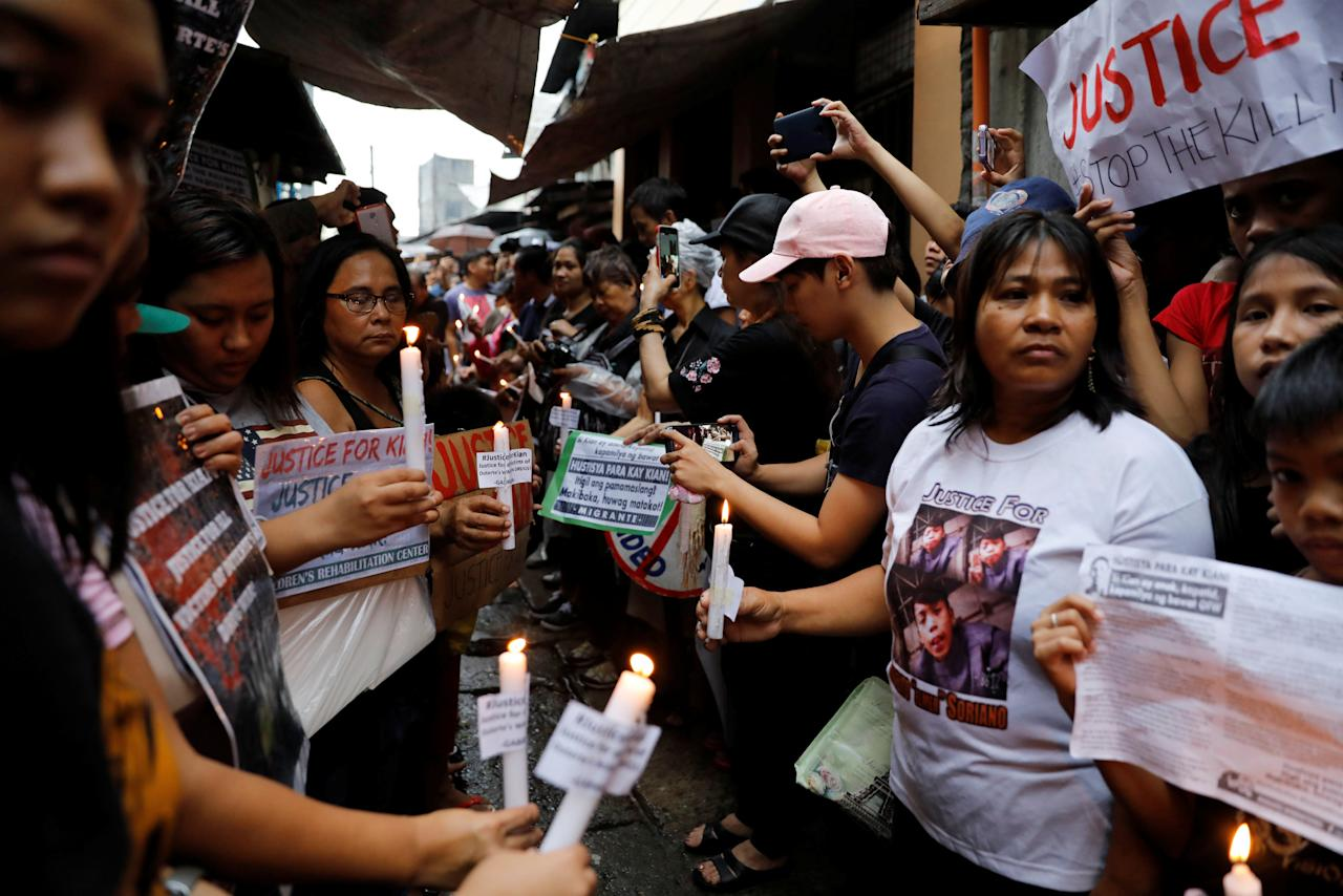 Protesters and residents hold lighted candles and placards at the wake of Kian Loyd delos Santos, a 17-year-old high school student, who was among the people shot dead last week in an escalation of President Rodrigo Duterte's war on drugs in Caloocan city, Metro Manila, Philippines August 21, 2017. REUTERS/Erik De Castro