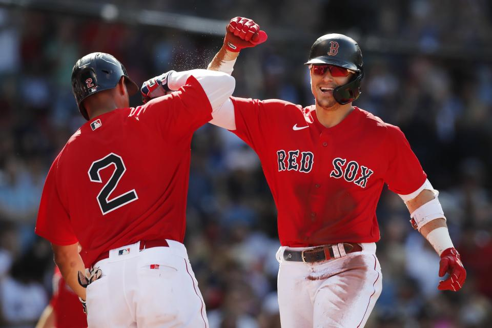 Boston Red Sox's Enrique Hernandez, right, celebrates with Xander Bogaerts (2) after a throwing error by New York Yankees' Rougned Odor allowed Hernandez to score on his triple during the first inning of a baseball game, Saturday, July 24, 2021, in Boston. (AP Photo/Michael Dwyer)
