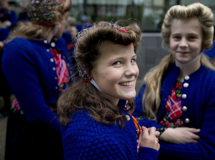 Sophie Feijer, from the village of Staphorst, center, wears a traditional dress as she attends celebrations marking the official opening of the new parliamentary year that contains a speech outlining the government's plan and budget policies for the year ahead in The Hague, Netherlands, Tuesday, Sept. 17, 2013. (AP Photo/Peter Dejong)