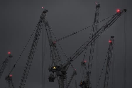 Construction cranes are seen at dusk on a grey day in London Britain