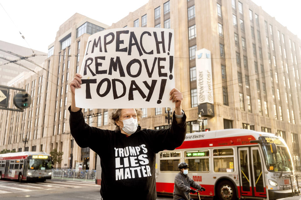 Kenneth Lundgreen holds a sign against President Donald Trump outside of Twitter headquarters on Monday, Jan. 11, 2021, in San Francisco. Police officers erected barricades and staged for a possible conservative protest Monday morning. (AP Photo/Noah Berger)