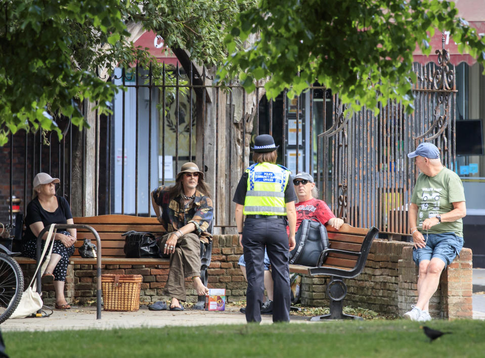 A Police Community Support Officer chats to people as they social distance in York, following the introduction of measures to bring England out of lockdown. (Photo by Danny Lawson/PA Images via Getty Images)