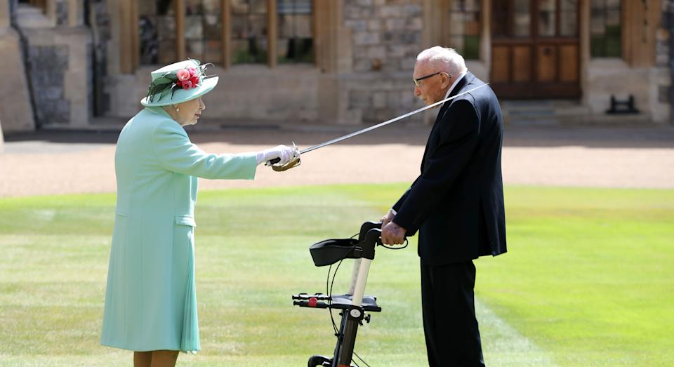 Captain Sir Thomas Moore arrives to receive his knighthood from Queen Elizabeth II during a ceremony at Windsor Castle.