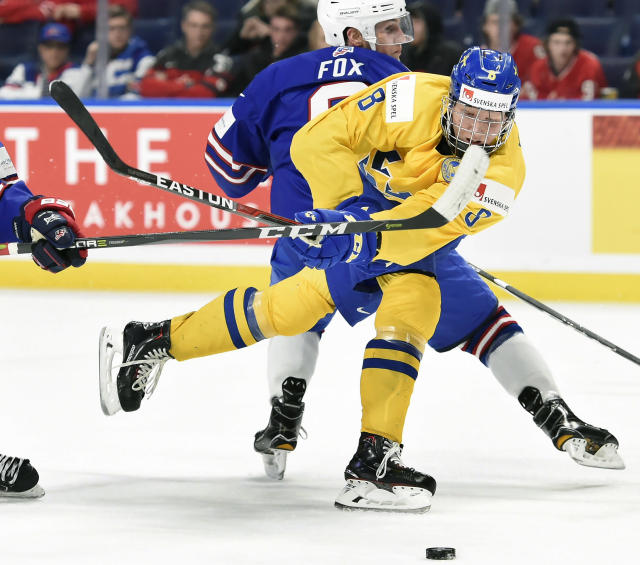 FILE - In this Jan. 4, 2018, file photo, Sweden's Rasmus Dahlin (8) moves the puck around United States' Adam Fox, rear, during the second period of a semifinal game at the world junior hockey championship in Buffalo, N.Y. With likelihood of selecting Dahlin with the first pick in the draft on Friday, June 22, the Buffalo Sabres are again in a position to end whats been a decade-long freefall. (Nathan Denette/The Canadian Press via AP, File)