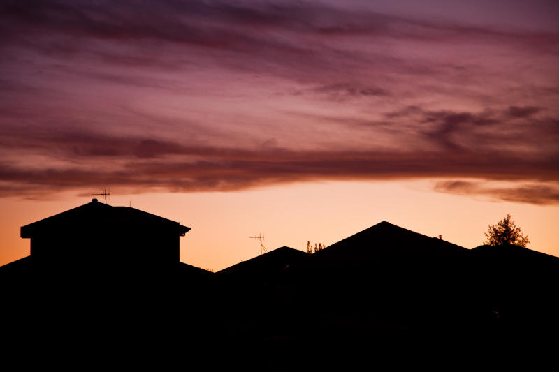 Silhouettes of the roofline of suburban houses at sunset.