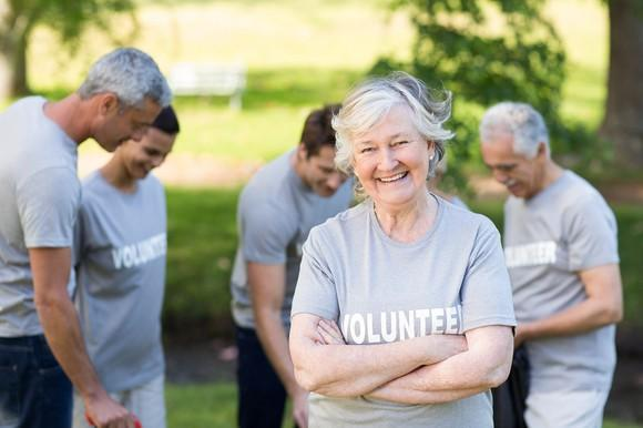 "Older woman with ""volunteer"" on her shirt smiles at the camera."