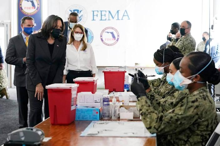 Vice President Kamala Harris, left, receives a tour from FEMA regional administrator Gracie Szchech, as members of the Navy, seated right, prepare Pfizer vaccines at the Jacksonville Community Vaccination Center, Monday March 22, 2021, in Jacksonville, Fla. Also present: Jacksonville Mayor Lenny Curry, left, and Rep. Al Lawson, D-Fla., third from left.