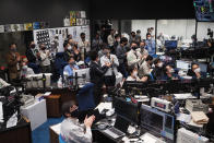 In this photo provided by the Japan Aerospace Exploration Agency (JAXA), Hayabusa2 project members react as they watch over the live streaming about the fireball phase of the re-entry capsule at a control room of JAXA's Sagamihara Campus in Sagamihara, near Tokyo, early Sunday, Dec. 6, 2020. A Japanese capsule carrying the first samples of asteroid subsurface shot across the night atmosphere early Sunday before successfully landing in the remote Australian Outback, completing a mission to provide clues to the origin of the solar system and life on Earth. (JAXA via AP)
