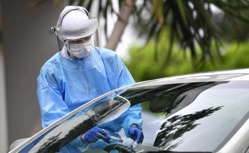 A health care worker is seen testing people at a Covid-19 drive through testing clinic at Murarrie in Brisbane.