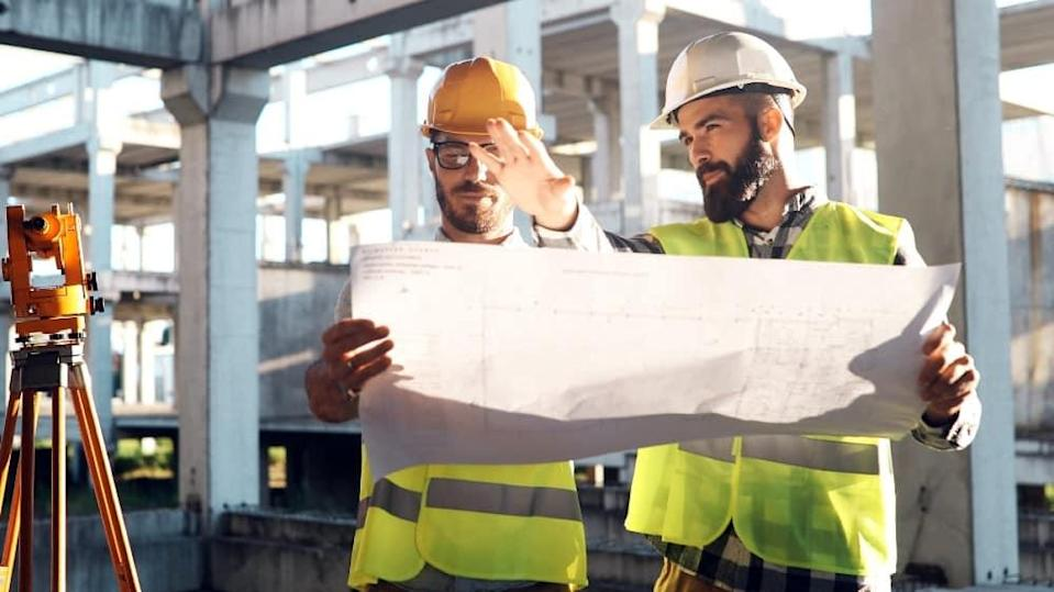 Portrait of construction engineers working on building site together