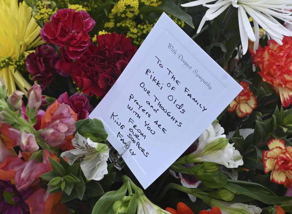 A solemn group of King Soopers employees, left, some from the Boulder store and some from the same district brought large sprays of flowers for each of the victims of a mass shooting at a Boulder Kings Soopers store on Monday. Each spray had a card with condolences for the victims' families and signed by their King Sooper family. The group brought their flowers to a fence around the King Soopers where a makeshift memorial has been made for the ten victims of a mass shooting. Tuesday, March 23, 2021. (Jerilee Bennett/The Gazette via AP)