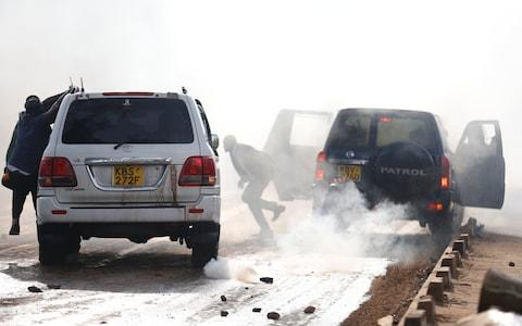 Kathiani Member of Parliament Robert Mbui (beneath the darker vehicle number plate) is hit by another car as riot police disperse the convoy of Kenyan opposition leader Raila Odinga  - Credit: REUTERS