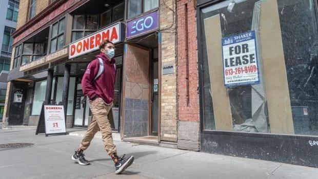 A masked pedestrian walks by a retail space for lease on Bank Street in Ottawa in late April 2021.