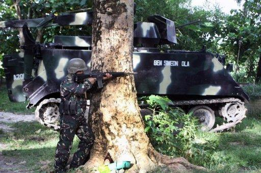 A Philippine soldier takes his position next to a tank in the town of Talayan, on the southern island of Mindnano on August 6, 2012, after members of a breakaway Muslim rebel group launched simultaneous attacks across 11 towns in the southern Philippines. Philippine troops have found four bodies including the mutilated corpses of two soldiers