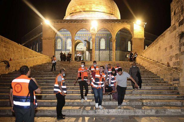 PHOTO: Palestinian medics evacuate a wounded person during clashes between Israeli security forces and Palestinian protestors in Jerusalem's al-Aqsa mosque compound, May 10, 2021.  (Ahmad Gharabli/AFP via Getty Images)