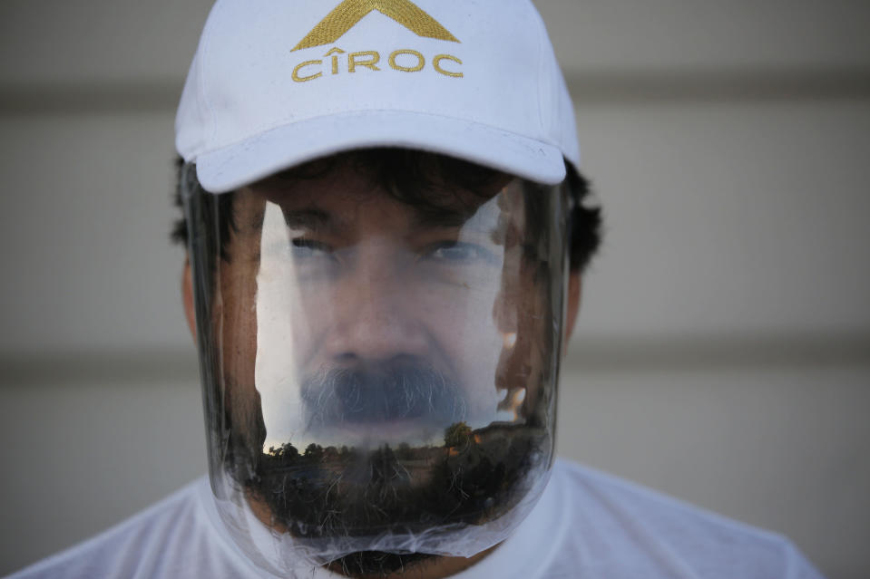 In this April 24, 2020, photo, Victor Chicas poses at his home wearing a homemade mask he uses for protection from the coronavirus in Las Vegas. Chicas, a restaurant server in the Mandalay Bay casino-hotel, was facing foreclosure on his home before the virus shut down the city and the 54-year-old was laid off. (AP Photo/John Locher)