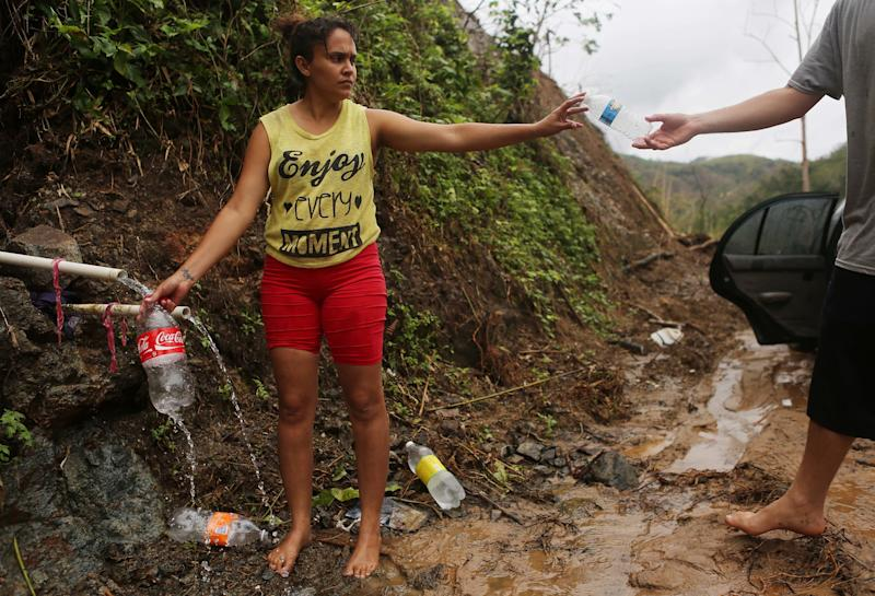 Puerto Rican resident Yanira Rios collects spring water nearly three weeks after Hurricane Maria destroyed her town of Utuado, which still has little running water or power.
