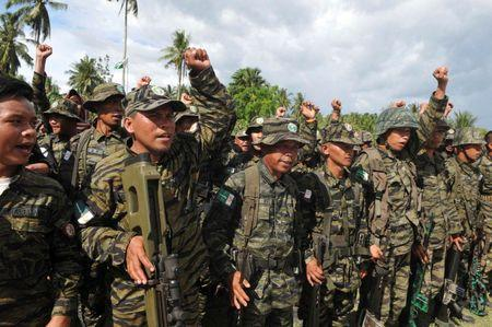 Moro Islamic Liberation Front (MILF) forces raise their fists during a show of force inside the camp in Camp Darapanan, Maguindanao province, southern Philippines