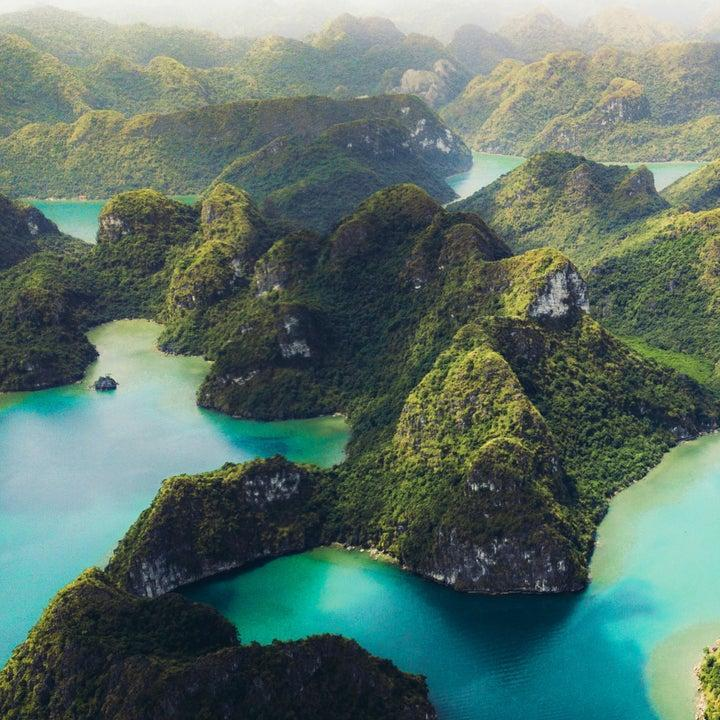 bright summer sunrise at Halong Bay, a huge bay with mountains and hills scatters throughout
