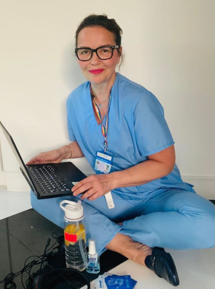 Vera Ora, an NHS psychiatrist, sits on the floor wearing blue hospital scrubs with a laptop on her knee