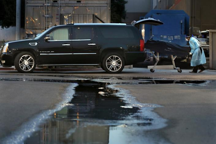"Juan Lopez, 45, loads a body into the Cadillac Escalade he uses for his business, Elite Transportation Services, which is busier than ever this month due to the spike in COVID-19 deaths in Texas' Rio Grande Valley. <span class=""copyright"">(Carolyn Cole / Los Angeles Times)</span>"