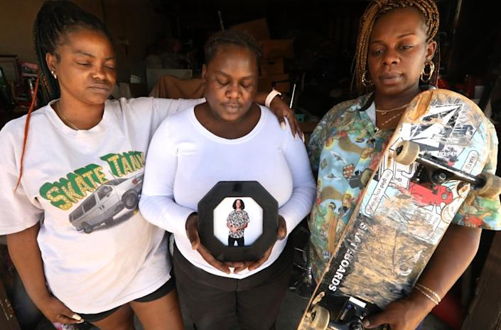 LANCASTER, CA - JUNE 29, 2020 - - Sisters Candice Russaw, 33, from left, Chanel Evans, 28, and Brandy Russaw, 34, remember their brother, 20-year-old Jacob Russaw, in photo, who committed suicide in 2018. Candice wears Jacob's t-shirt and Brandy holds his skateboard and wears one of his shirts. The sisters were photographed at Brandy's home in Lancaster on June 29,. 2020. He was a skilled skateboarder with hopes of going pro or getting a sponsorship. At the time of his death he'd been put out of a youth homeless shelter in Hollywood, Covenant House, for infractions, despite being well-loved by shelter residents and officials, who put on a memorial and paid for his funeral. Candice feels the agency could have done more to provide mental health and prevent his death. Russaw died by hanging himself. (Genaro Molina / Los Angeles Times)