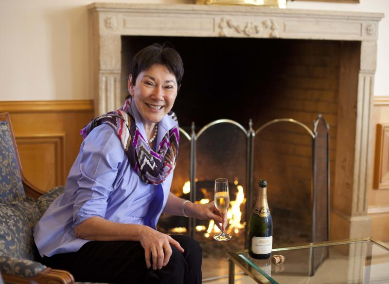 In this photo taken Wednesday, Nov. 14, 2012, CEO and winemaker Eileen Crane sits with a glass of Brut Cuvee sparkling wine at Domaine Carneros in Napa, Calif. Something new is bubbling up in the world of cocktails, using sparkling wine as a mixer. (AP Photo/Eric Risberg)