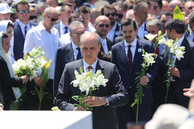<p>Deputy Prime Minister of Turkey Numan Kurtulmus (C) holds a lily in his hands, which represents victims' innocence, to mark the 22nd anniversary of the 1995 Srebrenica genocide in Potocari village of Srebrenica, Bosnia and Herzegovina on July 11, 2017. (Photo: Kemal Zorlak/Anadolu Agency/Getty Images) </p>