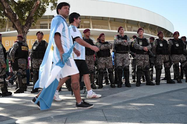Argentina's fans walk past members of the security services prior to the 2014 FIFA World Cup final football match between Germany and Argentina at the Maracana Stadium in Rio de Janeiro, Brazil on July 13, 2014 (AFP Photo/Damien Meyer)