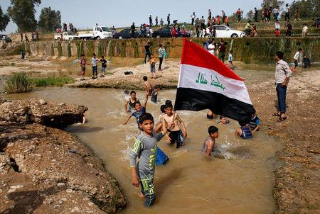 "A boy holds the Iraqi flag as he plays in the water with other children during a Friday holiday at Shallalat district (Arabic for ""waterfalls"") in eastern Mosul, Iraq, April 21, 2017. REUTERS/Muhammad Hamed"