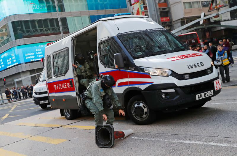 A riot police officer removes a traffic cone thrown by a protester to block the traffic, outside Mong Kok station in Hong Kong