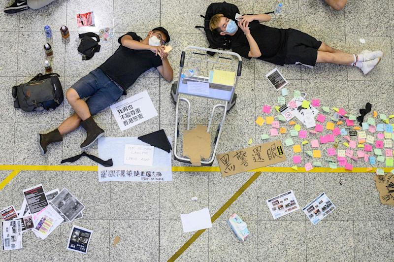 Protesters rest among signs at Hong Kong's International airport during a protest against the police brutality and the controversial extradition bill.