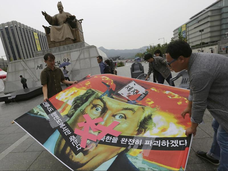 South Korean protesters carry a caricature of Donald Trump during a rally to denounce the US' policy against North Korea, near the American Embassy in Seoul on 26 September: AP Photo/Ahn Young-joon