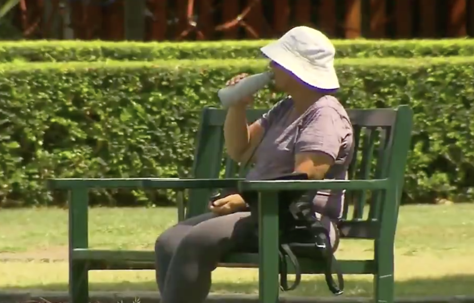 A woman drinks from a water bottle in hot conditions in Queensland.