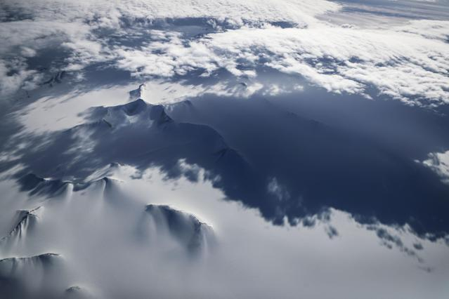 <p>Mountains peek through land ice as seen from NASA's Operation IceBridge research aircraft in the Antarctic Peninsula region, on Nov. 4, 2017, above Antarctica. (Photo: Mario Tama/Getty Images) </p>