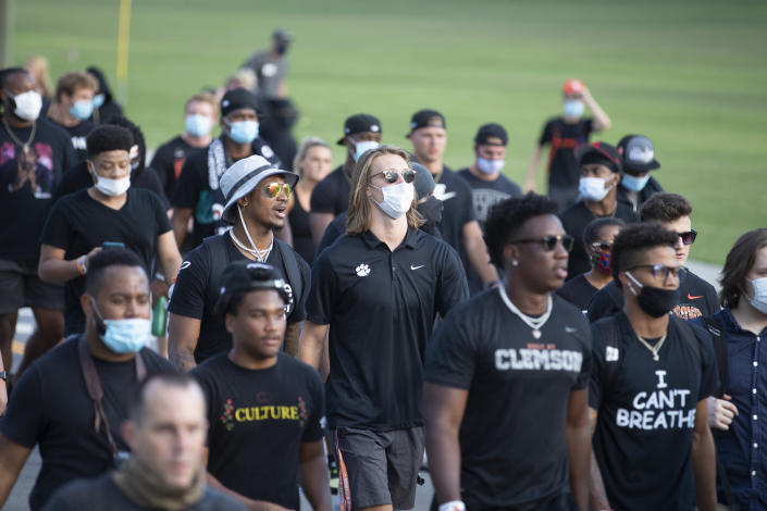Clemson quarterback Trevor Lawrence, center, marches with teammates during a protest Saturday, June 13, 2020, in Clemson, S.C., over the death of George Floyd who died after being restrained by Minneapolis police officers on May 25. (AP Photo/John Bazemore)