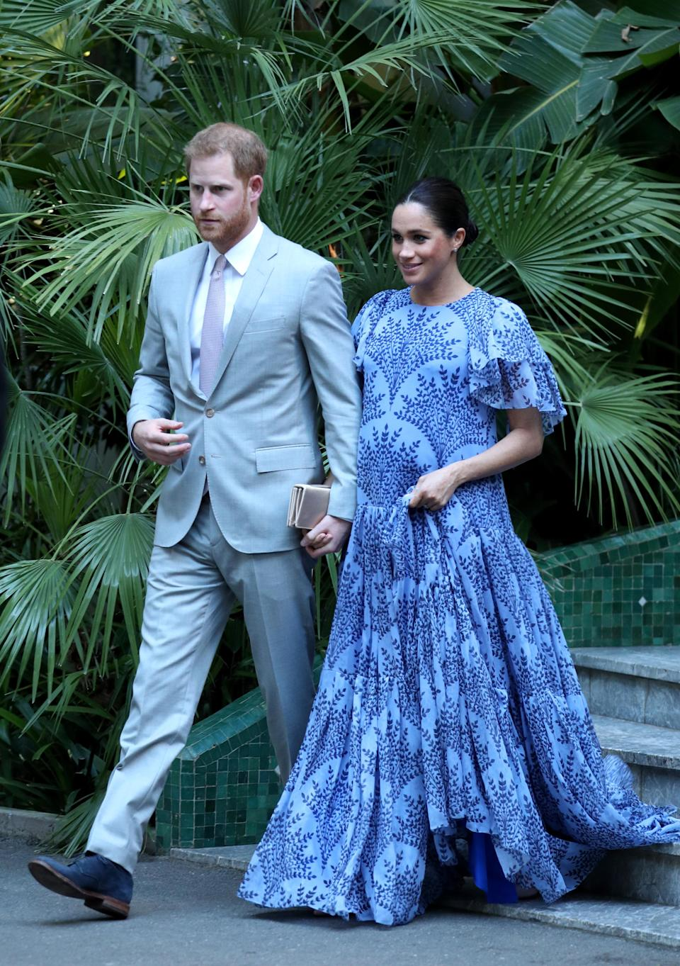 """<p>To meet Mohammed VI of Morocco, the King of Morocco, Meghan looked gorgeous in a bespoke blue floral <a rel=""""nofollow noopener"""" href=""""https://www.modaoperandi.com/carolina-herrera-fw19/floral-printed-silk-chiffon-short-sleeve-gown?utm_campaign=productads&mid=37385&utm_medium=Linkshare&utm_source=ShopStyle++Collective&utm_content=*2nGiS3mv0Y&siteID=.2nGiS3mv0Y-yR7IoJbiR3YbR6Mg.O_85w"""" target=""""_blank"""" data-ylk=""""slk:Carolina Herrera gown"""" class=""""link rapid-noclick-resp"""">Carolina Herrera gown</a> with nude pumps and her gold satin Dior 'Bee' clutch. She also rewore her Cartier diamond and white gold wedding earrings. [Photo: Getty] </p>"""