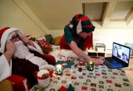 An assistant helps Pillmayer, dressed as Santa, as he prepares to interact with children by video, amid the COVID-19 outbreak in Budapest