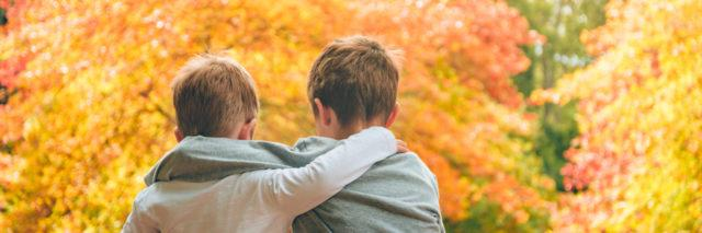 Embracing brothers sitting in autumn forest.