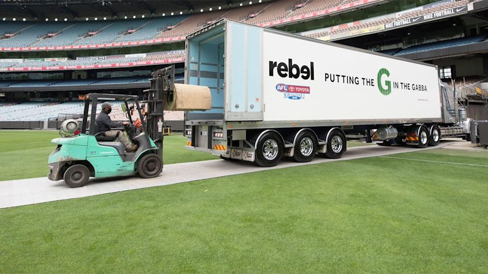 The MCG turf, pictured here being transported to the Gabba by Rebel Sport staff.