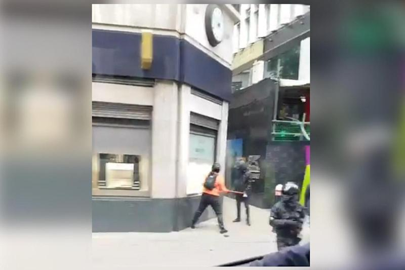 One suspect is seen striking the window of Mappin & Webb in Fenchurch Street with an axe