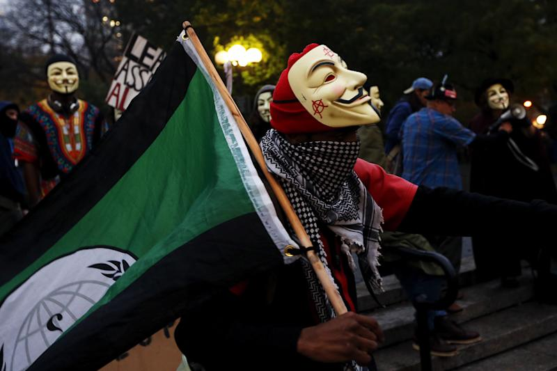 "A protester from the online activist group ""Anonymous"" wearing a Guy Fawkes mask walks with a flag during a protest rally in New York, November 5, 2015. The group claims to be mobilizing protests in more than 600 cities worldwide as part of what they call the ""Million Mask March"" held on Guy Fawkes day. REUTERS/Shannon Stapleton TPX IMAGES OF THE DAY"