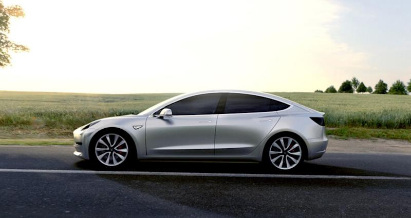 A silver Tesla Model 3 traveling on a road with a green field in background.