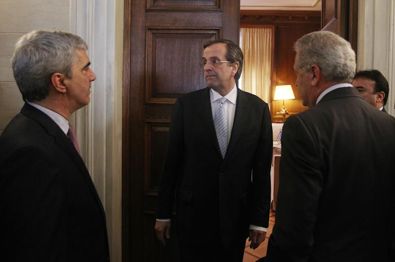 Greece's Prime Minister Antonis Samaras, center, stands outside his office surrounded by Foreign Minister Dimitris Avramopoulos, right, and Government's spokesman Simos Kedikoglou, left, after his meeting with recently-elected Cypriot President Nicos Anastasiades, not seen, at Maximos mansion in Athens, Monday, March 11, 2013. Updated official data show Greece's economy shrank at a slightly slower pace than initially forecast in the last quarter of 2012, but still contracted by 6.4 percent during the year. (AP Photo/Thanassis Stavrakis)