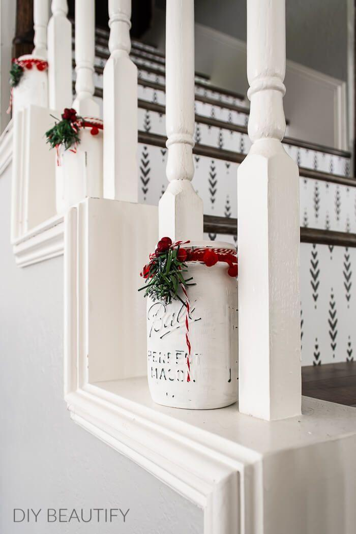 """<p>Simple Mason jars painted white add just the right touch of farmhouse chic to these stairs. Add an LED candle and you're done!</p><p><strong>See more at <a href=""""https://www.diybeautify.com/2020/12/dining-room-holiday-home-decor-ideas.html.html"""" rel=""""nofollow noopener"""" target=""""_blank"""" data-ylk=""""slk:DIY Beautify"""" class=""""link rapid-noclick-resp"""">DIY Beautify</a>.</strong></p><p><a class=""""link rapid-noclick-resp"""" href=""""https://www.amazon.com/FolkArt-34846-Furniture-Assorted-Adirondack/dp/B00RGFYFL2/ref=sr_1_6?dchild=1&keywords=WHITE+CHALK+PAINT&qid=1633171312&sr=8-6&tag=syn-yahoo-20&ascsubtag=%5Bartid%7C2164.g.37723896%5Bsrc%7Cyahoo-us"""" rel=""""nofollow noopener"""" target=""""_blank"""" data-ylk=""""slk:SHOP WHITE CHALK PAINT"""">SHOP WHITE CHALK PAINT</a></p>"""
