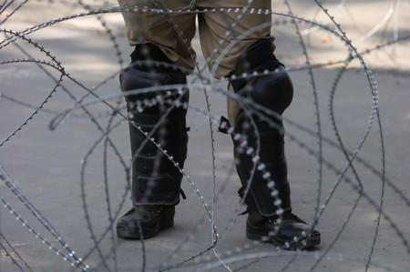 An Indian police officer stands behind the concertina wire during restrictions on Eid-al-Adha after the scrapping of the special constitutional status for Kashmir by the Indian government, in Srinagar