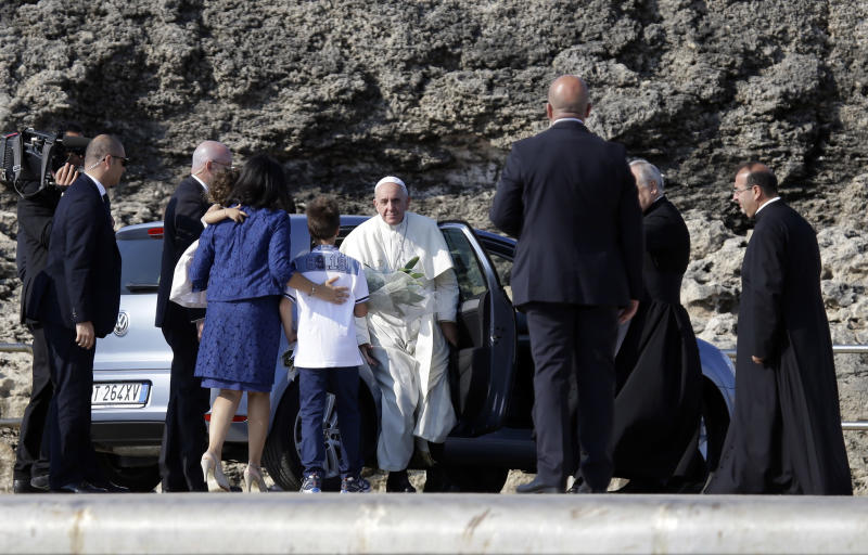 Pope Francis is welcomed upon his arrival in the island of Lampedusa southern Italy, Monday July 8, 2013. Pope Francis has arrived on the tiny Sicilian island of Lampedusa to greet recently arrived migrants as yet another boatload came ashore carrying 162 Eritreans. Francis came to pray with survivors of the treacherous crossing from Africa and mourn those who have died trying. He flew Monday from Rome to Lampedusa's airport and was traveling by coast guard ship to the island's main port, where he is to throw a wreath of flowers into the sea to remember migrants who never arrived. (AP Photo/Gregorio Borgia)