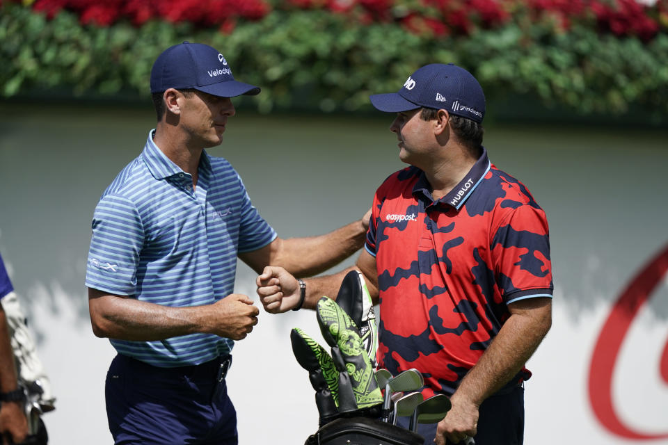 Billy Horschel, left, and Patrick Reed, right, greet each other on the first tee during the first round of the Tour Championship golf tournament Thursday, Sept. 2, 2021, at East Lake Golf Club in Atlanta. (AP Photo/Brynn Anderson)