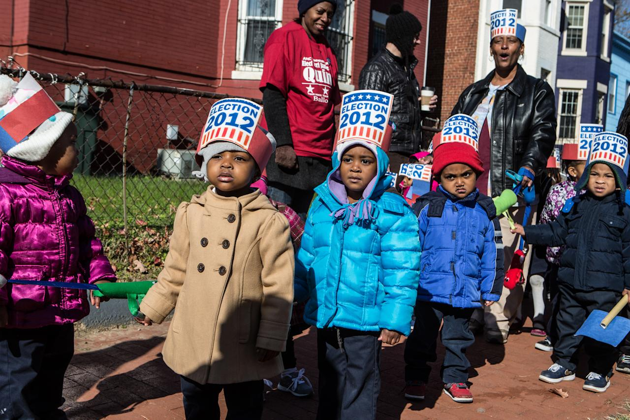 Children from Kingdom Kinds Child Development Center march past a polling station to get out the vote at Dunbar High School on November 6, 2012 in Washington, DC. The latest polls continue to show a tight race between President Barack Obama and Republican challenger Mitt Romney. (Photo by Brendan Hoffman/Getty Images)